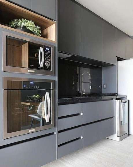 27. Decoração de cozinha planejada cinza com forno elétrico embutir e nicho de madeira – Foto: Pinterest