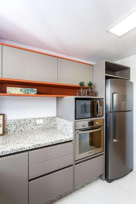 30. Forno elétrico de embutir inox para cozinha com nichos laranjas e armários cinza – Foto: Gazeta do Povo
