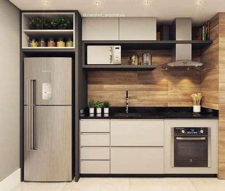 41. O revestimento de madeira dá um toque aconchegante à cozinha planejada com forno elétrico embutir – Foto: Home Solution