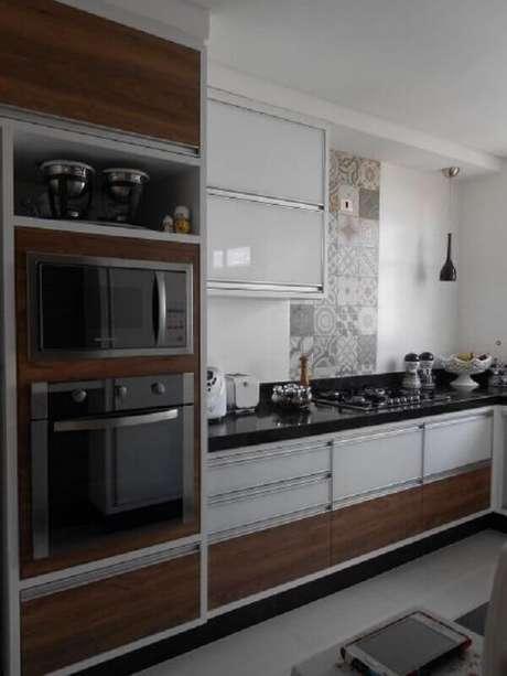 44. Cozinha simples decorada com armários brancos com detalhe em madeira e forno elétrico embutir – Foto: Pinosy