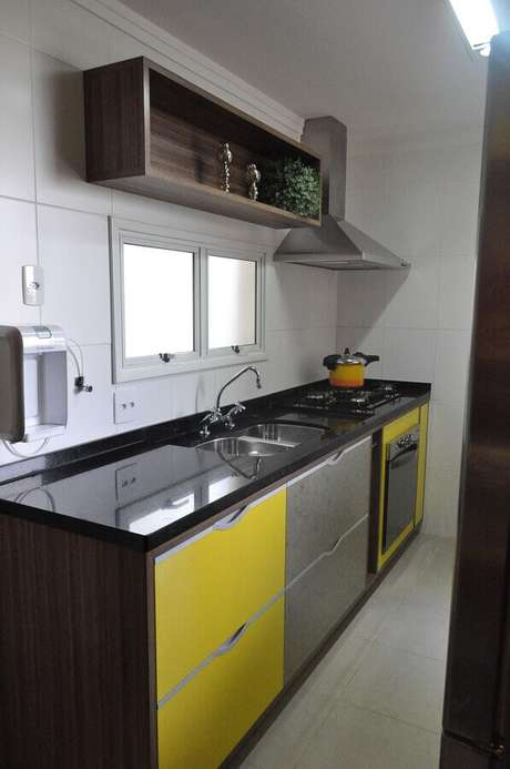 48. Forno elétrico embutir para cozinha simples com armário amarelo e bancada preta – Foto: Daniela Oliveira Landsberg