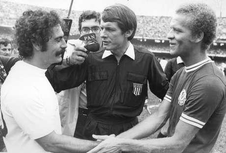 Os jogadores Roberto Rivelino (e), do Corinthians e Ademir da Guia (d), do Palmeiras, se cumprimentam sendo observado pelo juiz Dulcídio Wanderley Boschilla, antes da partida válida pela final do Campeonato Paulista de Futebol de 1974 no estádio do Morumbi, zona sul da cidade de São Paulo.