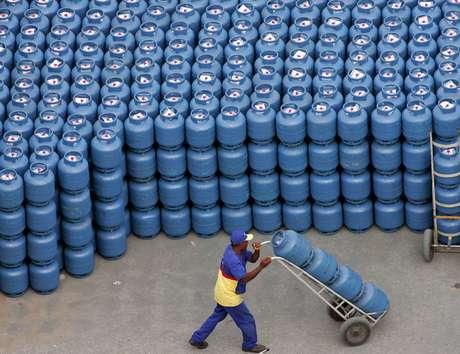 Trabalhador transporta botijões de gás de cozinha nas instalações de uma distribuidora em São Paulo
