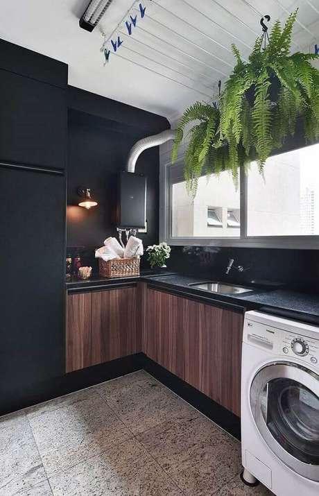 15. Cozinha preta com granito preto na bancada e armários de madeira, deixando o ambiente mais aconchegante
