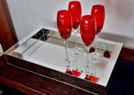 32. Bandeja espelhada para aparador com taças vermelhas na decoração