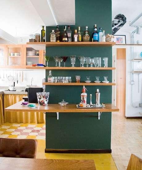 19. Parede da sala com prateleiras para guardar bebidas, taças e copos.