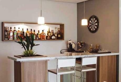 36. Barzinho para sala pequena com estante de madeira em parede.