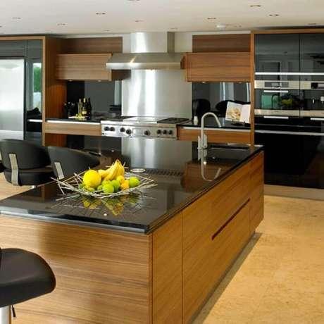 2. Cozinha com granito preto e armários de madeira