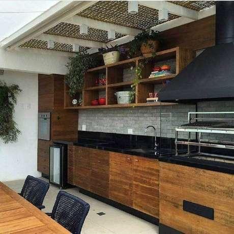 20. Cozinha com granito preto absoluto e armários de madeira, o toque moderno ficou por conta dos tijolinhos cinza na parede