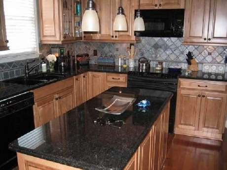 21. Prefira armários em tons claros ou neutros como os de madeira para cozinha com granito preto