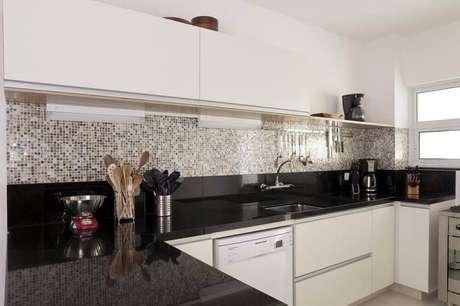 23. Cozinha com bancada de granito preto e pastilhas na parede