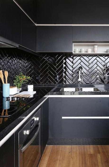 26. Cozinha preta elegante com piso laminado e bancada de granito preto.