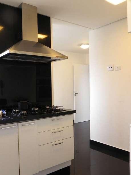 29. Decoração de cozinha planejada com granito preto para bancada e armários brancos