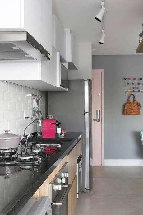 31. Cozinha simples decorada com bancada de granito preto e spots de luz