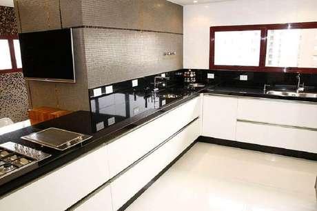 35. Cozinha americana com granito preto para bancada e armários planejados