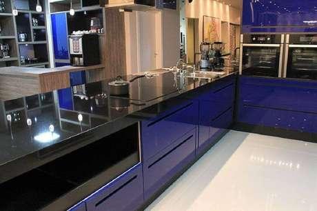 39. Cozinha planejada azul com granito preto São Gabriel para as bancadas
