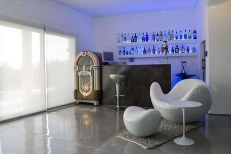 65. Prateleiras com iluminação em azul encantam a área do barzinho para sala.