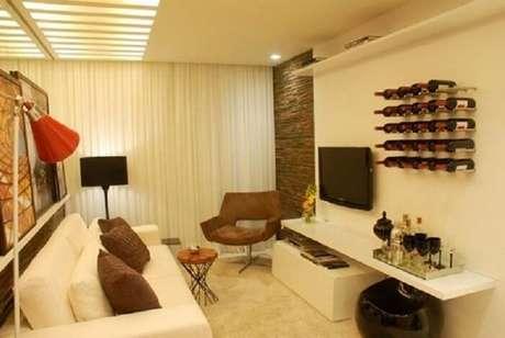 67. Suporte de garrafas na parede encantam a área de barzinho para sala.