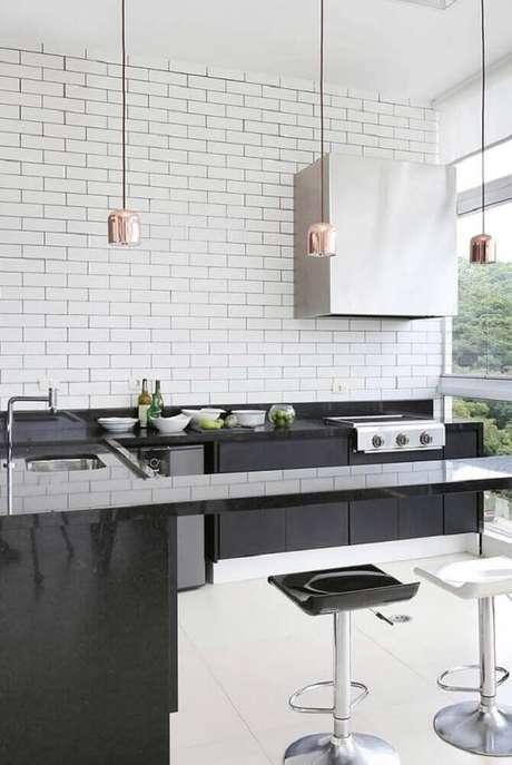42. Decoração de cozinha moderna com pendentes rose e bancada feita em granito preto