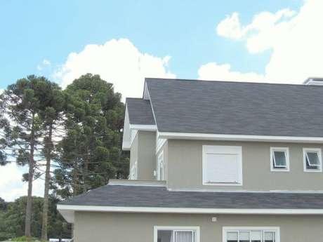 41. Telhado de casa cinza com janelas brancas e parede neutra
