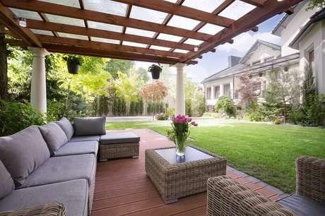 32. Área externa com varanda de madeira e sofá amplo com vários lugares. Fonte: Pinterest