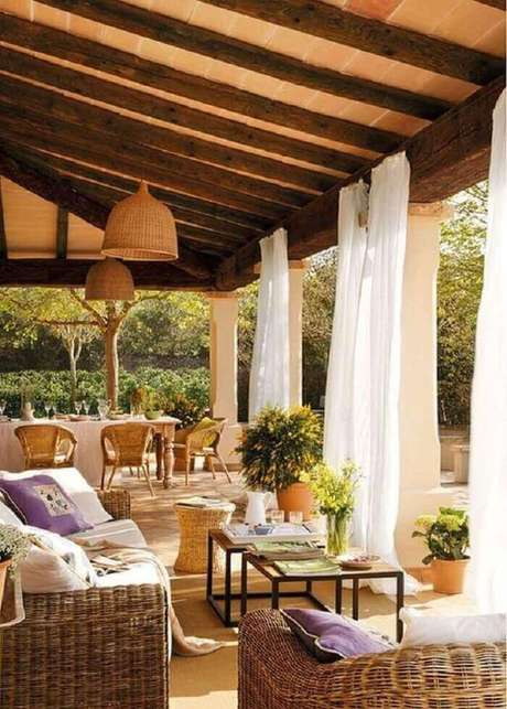 33. As cortinas brancas minimizam a entrada de luz solar na varanda de madeira. Fonte: Pinterest
