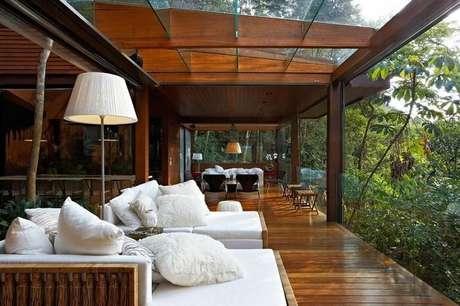 55. Casa de campo com varanda de madeira com teto e guarda corpo de vidro. Projeto por Carico Arquitetura