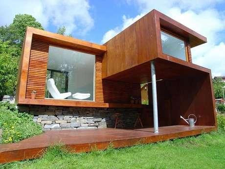 3. Casa de madeira com varanda. Arquitetura moderna e parede com pedras naturais. Fonte: Revista Viva Decora