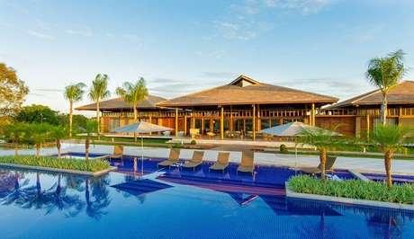 11. Casa de madeira com varanda conta com a presença de piscina e paisagismo encantador. Projeto por Sandra Moura