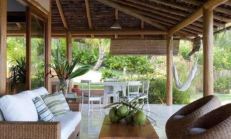 35. Casa de praia com varanda de madeira, móveis rústicos e rede para descanso. Fonte: Tecto
