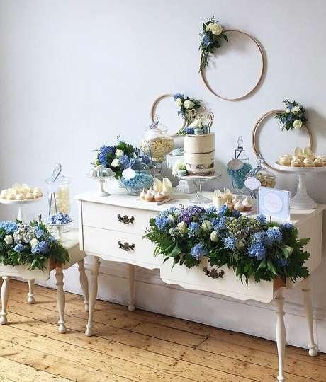27. Decoração para chá de fraldas com arranjo de flores azuis e detalhes românticos – Foto: Buffets by Design