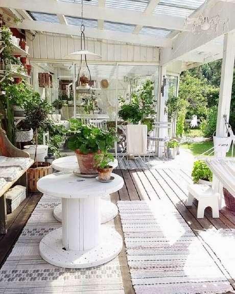 67. Mesa de centro em forma de carretel complementa a decoração da varanda de madeira. Fonte: Pinterest