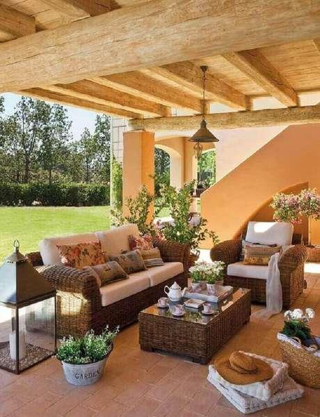 40. Móveis rústicos e flores encantam a decoração dessa varanda de madeira. Fonte: Pinterest