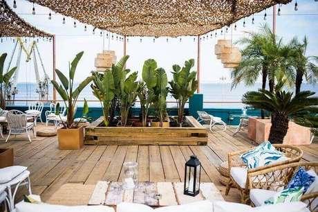 41. Móveis rústicos e vasos com folhagens complementam a decoração dessa varanda de madeira. Fonte: Pinterest