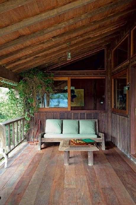 43. O sofá de três lugares com tecido verde complementa a decoração da varanda de madeira. Fonte: Pinterest