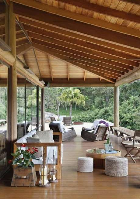 45. Varanda de madeira ampla com pé direito alto e móveis rústicos. Fonte: Pinterest