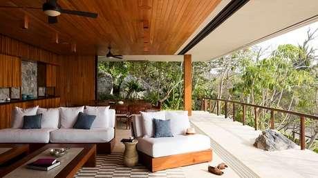 51. Varanda de madeira com móveis em tonalidade neutra. Fonte: ArchDaily