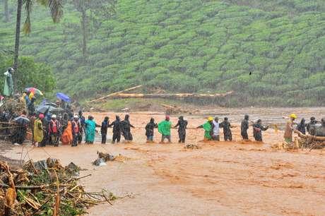 Equipes de resgate ajudam pessoas a cruzar área alagada em Wayanad, no Estado de Kerala, na Índia 09/08/2019 REUTERS