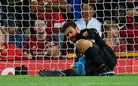 Alisson caiu ao chão após cobrar tiro de meta (Foto: OLI SCARFF / AFP)