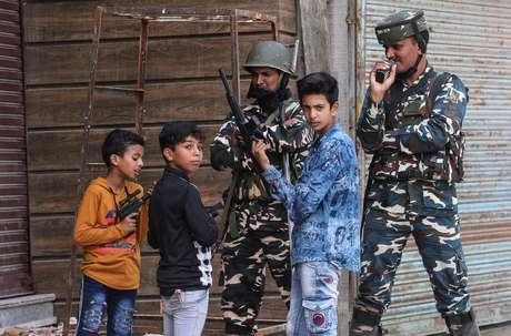 Crianças brincam com armas de brinquedo perto de membros das forças de segurança da Índia, na Caxemira 13/08/2019 REUTERS/Danish Ismail