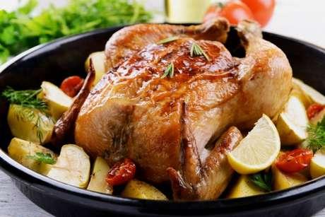 Forre o fundo da forma com legumes ou limão, para que o frango fique no alto