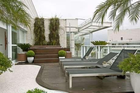 18. Este piso para varanda em pedra portuguesa conversa muito bem com o deck de madeira. Projeto de Bianka Mugnatto