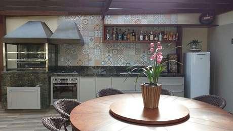 62. Área de lazer aconchegante com mesa de madeira redonda e parede revestida com ladrilhos hidráulicos. Fonte: Pinterest