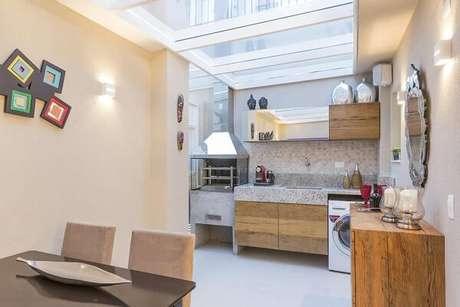 8. Área de lazer integrada com teto de vidro e churrasqueira com coifa de inox e laterias em vidro. Projeto por Cristiane Bergesch Bergesch