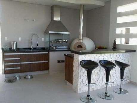 15. Área de lazer pequena com churrasqueira de vidro com coifa e forno de pizza. Fonte: Rachel Avellar