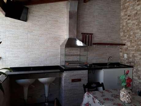 64. Área de lazer pequena com churrasqueira de vidro e bancada de granito preto. Fonte: Pinterest
