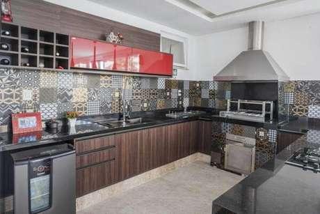 65. Área gourmet com bancada de granito preta ampla e armários na cor vermelha. Fonte: Pinterest