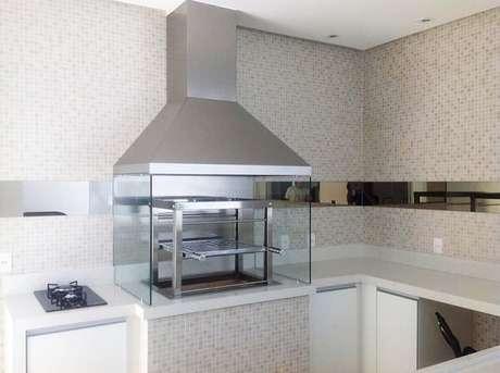 51. Churrasqueira com coifa de inox e lateral de vidro instalada ao lado do cooktop. Fonte: Pinterest