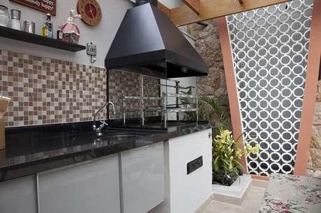 36. Churrasqueira de vidro com coifa instalada em bancada de granito preta. Fonte: Pinterest