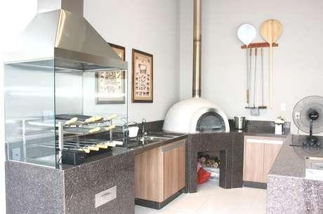 7. Espaço gourmet com churrasqueira de vidro e bancada de granito preto. Projeto por Mariana Campos